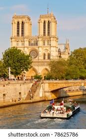 PARIS - APRIL 24: Tourists enjoy a boat trip on Seine river near Notre Dame cathedral on April 24, 2011 in Paris, France. Notre Dame de Paris receives about 12 million visitors annually.