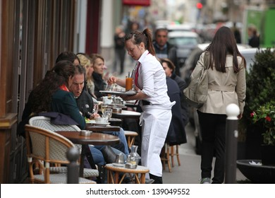 PARIS - APRIL 27 : Parisians and tourist enjoy eat and drinks in cafe sidewalk in Paris, France on April 27, 2013. Paris is one of the most populated metropolitan areas in Europe.