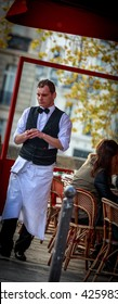 PARIS - APRIL 28, 2016: Springtime in Paris, a waiter at a sidewalk cafe.