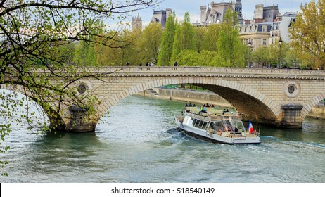 PARIS - APRIL 28, 2016: Tourists enjoy spring weather on a bateau mouche traveling up the Seine.
