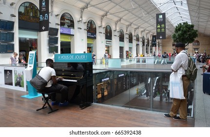 PARIS - AUG 10:  A visitor plays the piano at Gare Saint-Lazare in Paris, France on August 10, 2016. It is the second busiest train station in Paris