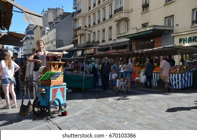PARIS - AUG 7:  A street organist plays a mechanical organ at the Marche Aligre in Paris, France on August 7, 2016.  The organ plays folded sheets of punched cards.