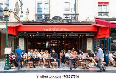 PARIS - AUGUST 23, 2017: People passes by a cafe on Rue Montorgueil street. People have brunch/lunch at cafe and enjoy nice weather on August 23, 2017.