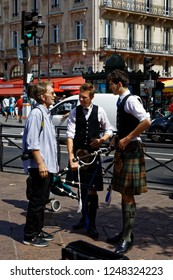 Paris - August 3, 2017: A man speaking with two young Scotsmen busking in Paris, France.