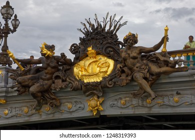 "Paris - August 3, 2017: The most ornate part of Pont Alexandre III, ""Nymphs of the Neva"" on a cloudy day in Paris, France."