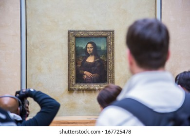 "PARIS - AUGUST 4: Visitors take photo of Leonardo DaVinci's ""Mona Lisa"" at the Louvre Museum, August 4, 2012 in Paris, France. The painting is one of the world's most famous."