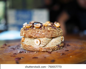 Paris Brest, a classic French dessert consist of large baked ring of choux pastry, filled with soft hazelnut cream topped with roasted hazelnut. Selective focus.