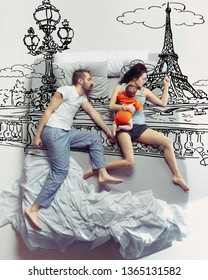 Paris is calling. Top view photo of young couple and their child sleeping in a big white bed. Dreams concept. Painted dream about trip in France, journey, adventures, family holidays and summertime.