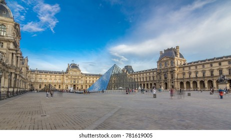 PARIS - CIRCA JULY 2017: The large glass pyramid and the main courtyard of the Louvre Museum timelapse hyperlapse before sunset. Tourists walking around at summer day with blue cloudy sky. Paris