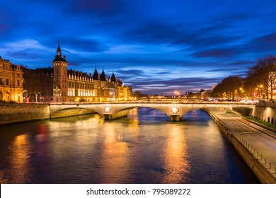 Paris city center by night with embankments of river Seine and illuminated street and historical Parisian building of Conciergerie on City island, blue hour, France.