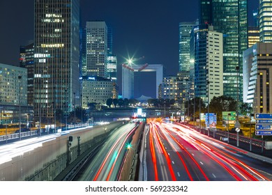 Paris cityscape with modern buildings in business district La Defense with dynamic street traffic and car lights by night. Glass facade skyscrapers. Concept of economics, finances. Copy space. Toned