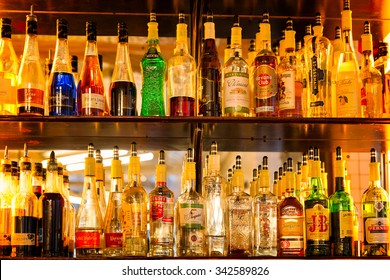 PARIS - Dec 23, 2013: Bottles of alcohol and spirits on backlit shelves at a pub or bar. Variety of French and imported labels.