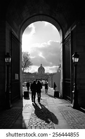 PARIS - DECEMBER 2,: Silhouettes of tourists walking through an arch at the Louvre towards the Pont Des Arts over the Seine River in Paris, France, on December 2, 2011.