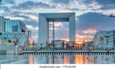 Paris Defense business district skyline with Grande Arche and office buildings feflected in water at sunset at summer day timelapse. View from fountain. Paris, France