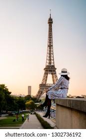 Paris Eifel tower sunset, woman with white dress watching Sunrise by Eifel tower Paris