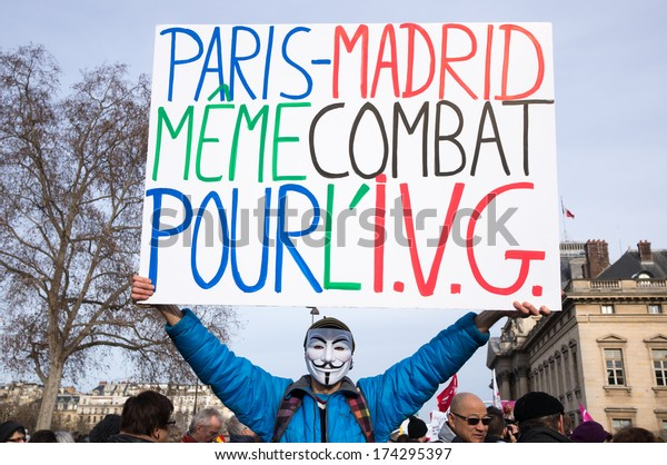 """PARIS - FEBRUARY 1, 2014: Man holds a panel with the inscription: """"Paris-Madrid, same combat, for the voluntary termination of pregnancy"""". Protesters marched against the new abortion law in Spain."""
