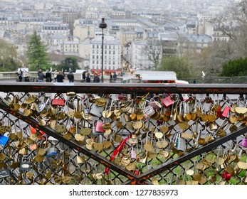Paris, France - 01/07/2019 : padlock of love hanging on a grid on the place of the Sacred Heart of Montmartre with Paris in the mist in the background