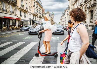 PARIS, FRANCE - 02 JULY 2016: Adult parisian woman cross the street at kick scooter by crosswalk with other pedestrians.