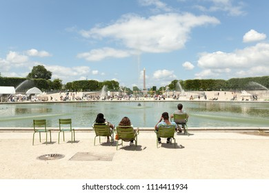 PARIS, FRANCE - 02 June 2018: Few people among other tourists and Parisians rest in Tuileries garden near Louvre museum. Tuileries garden became a public park after the French Revolution