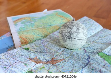 Paris, France. 02.04.2016. A vintage globe on a table covered with maps and a wooden floor at the background