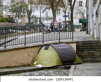 Paris, France - 02/10/2019 : On a sidewalk of Montmartre, at the foot of a small staircase, Quechua tent that allows a homeless to lodge in the street.