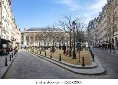 Paris, France, 03.24.2018. Place Dauphine in Paris with Parisians resting, benches and planted chestnuts, to which bicycles are parked