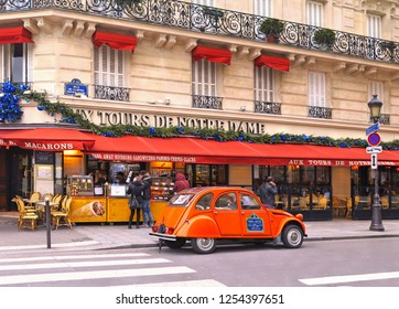 PARIS, FRANCE 05.01.2016. A French oldtimer classic orange car icon Citroen 2CV parked in the characteristic Street with restaurants inFrench capital Paris