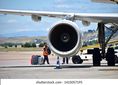 Paris / France - 06 04 2019: Close up on the propeller of an airliner plane with airport employees loading passenger's luggages