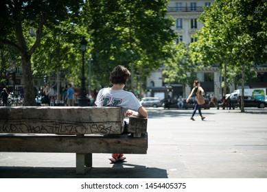 Paris, France, 07 07 2019. A man reads a book sitting on a bench in Paris.