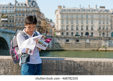 Paris, France, 07 July 2016 - A young asian man is looking at tourist map searching for sightseeing in the center of Paris. Paris, France, 07 July 2016