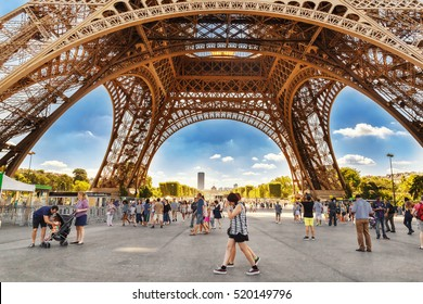 PARIS, FRANCE - 07 JULY 2016: Tourists walking under Eiffel tower (Eiffel tour) in sunny summer day in Paris. Eiffel tower is most popular travel destination in Paris city and France generally.