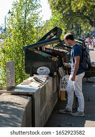 PARIS, FRANCE - 08/02/2018:   Tourist browsing at a  bookseller stall (Les bouquinistes) along the River Seine