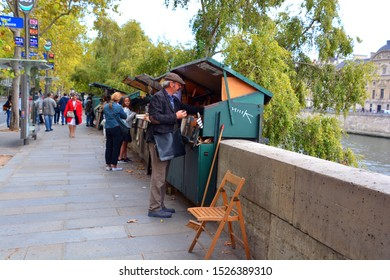 PARIS FRANCE 09 23 19: Vintage books and paintings in open bookmarket on embankment of River Seine near Notre Dame de Paris Cathedral. The bookmarket is there since the 16th century.