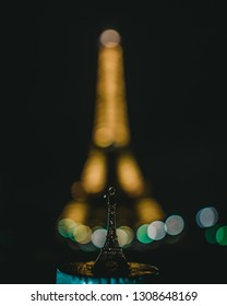Paris, France - 10 feb 2019 - Night look on the Eifel tower with little Eifel Tower figurine in the foreground