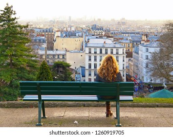 Paris / France 10.01.2016. Lonely Young woman sitting and relaxing on bench in the park on the hill of Sacré Coeur Cathedral Montmartre with city romantic  panorama.