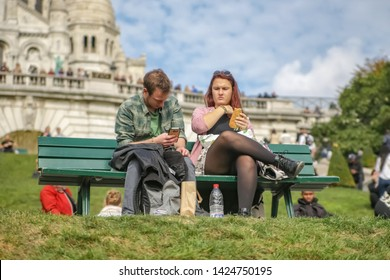 Paris, France, 10.08.2016. A man and a woman sitting on a bench on the hillside of Montmartre, in front of the Basilica of sacré-Coeur. A picnic on the bench