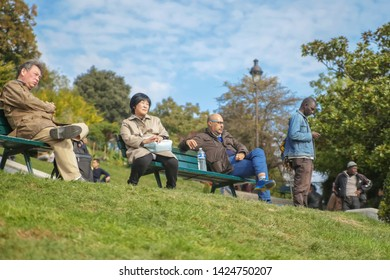 Paris, France, 10.08.2016. People relax by sitting on benches on the hillside of Montmartre in front of the Sacré Coeur Basilica in Paris