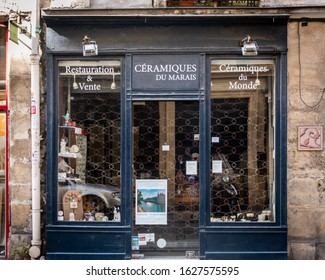 Paris, France 10-09-18. Old, vintage Paris ceramic store shop front facade in The Marais with blue wood trim around the windows and door
