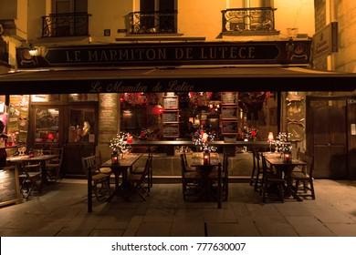 Paris, France, 10.12.2016 - tables, chairs and front entrance of Le Marmiton De Lutece Restaurance at night in Paris, France