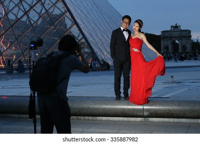 PARIS, FRANCE  10-15-2015: .Asiatic models in Paris doing a photo shoot with a photographer to advertise romantic trips to France and Europe.