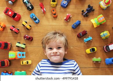 Paris, France. 10.15.2016. A young boy on a wood floor with all his cars and toys around him. Picture taken from above him, with a focus on his face and blurry toys