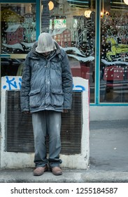 Paris, France. 10-December-2018. Portrait of a homeless man in front of a shop during Christmas
