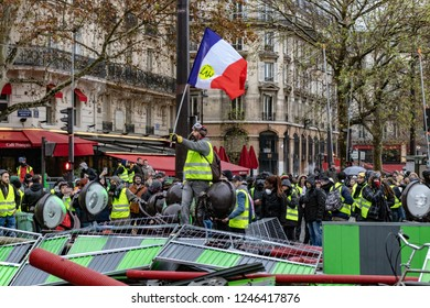 Paris, France- 12.01.2018 Rally Yellow Vests (Gilets Jaunes)  Against the new carburant taxes, the government and Emanuel Macron.  Man waving a flag on a pile of urban furniture