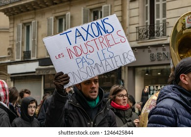 """Paris, France- 12.01.2018 Rally Yellow Vests (Gilets Jaunes)  Against the new carburant taxes, the government and Emanuel Macron. Sign """"tax the enterprises not the consumers"""""""