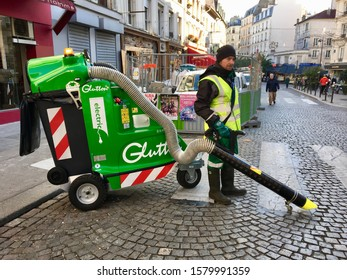 Paris, France - 12/04/2019 : City employee uses the new Glutton electric vacuum cleaner on the sidewalk on rue Lepic in Montmartre