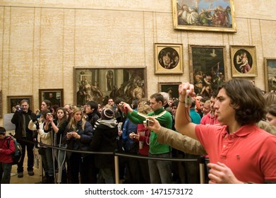 Paris / France - 12/28/2010 : Tourists are taking pictures of La Gioconda or the mona lisa, the famous painting by Leonardo Da Vinci at the Louvre museum in Paris.