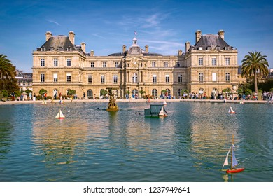 PARIS, FRANCE - 13 Oct 2018: Luxembourg palace and the vintage toy boats sailing in the Grand Bassin duck pond in Luxembourg Gardens