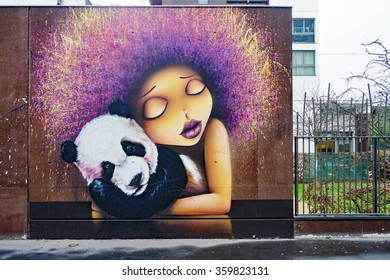PARIS, FRANCE -15 DEC 2015- Street art wall painting of a girl with a panda by French muralists Vinie and Doudou in the 13th arrondissement of the French capital.