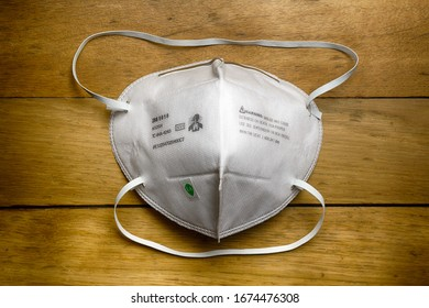 PARIS, FRANCE - 15 MAR 2020: 3M trademark N95 certified protection air filter mask lying on wooden table.