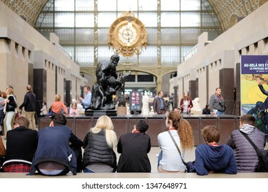 Paris, France - 16 Apr 2018: Several of Students sitting on the walkway with background of symbolic clock in Museum of Orsay (Musee de Orsay)